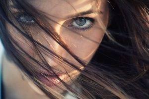 women face brunette hair in face blue eyes